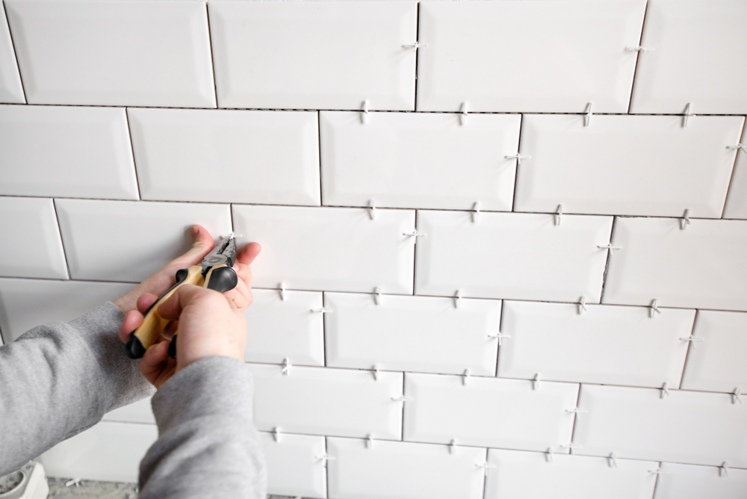Builder fitting subway-style tiles into a bathroom.
